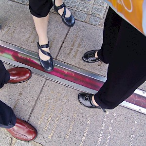 The popular tradition of standing in two hemispheres along the official Prime Meridian (Longitude 0º) at the Royal Observatory in Greenwich (Photo © Reid Bramblett)