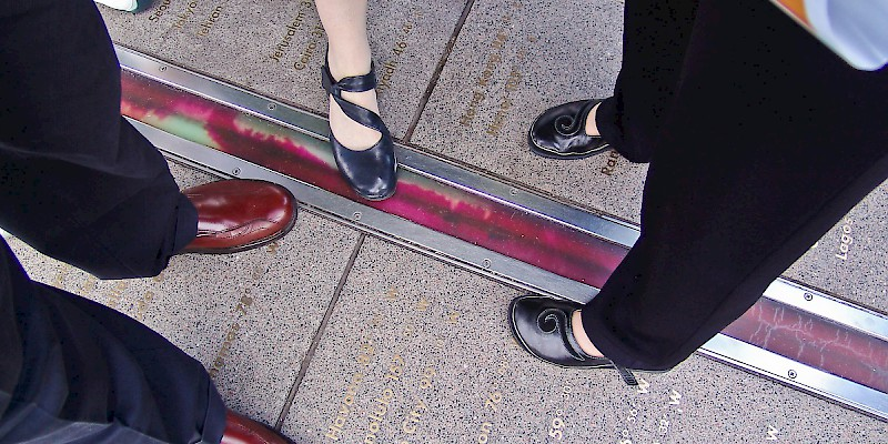 The popular tradition of standing in two hemispheres along the official Prime Meridian (Longitude 0º) at the Royal Observatory in Greenwich, Royal Observatory, London (Photo © Reid Bramblett)
